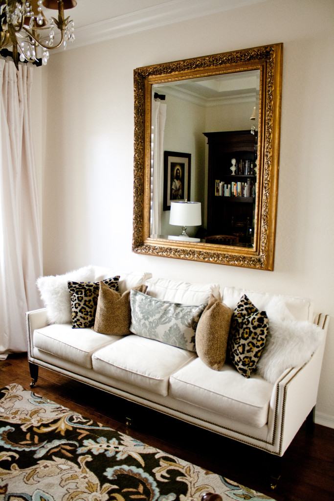 den with white sofa, gold antique mirror, leopard pillows, white walls, antique chandelier, fur pillows