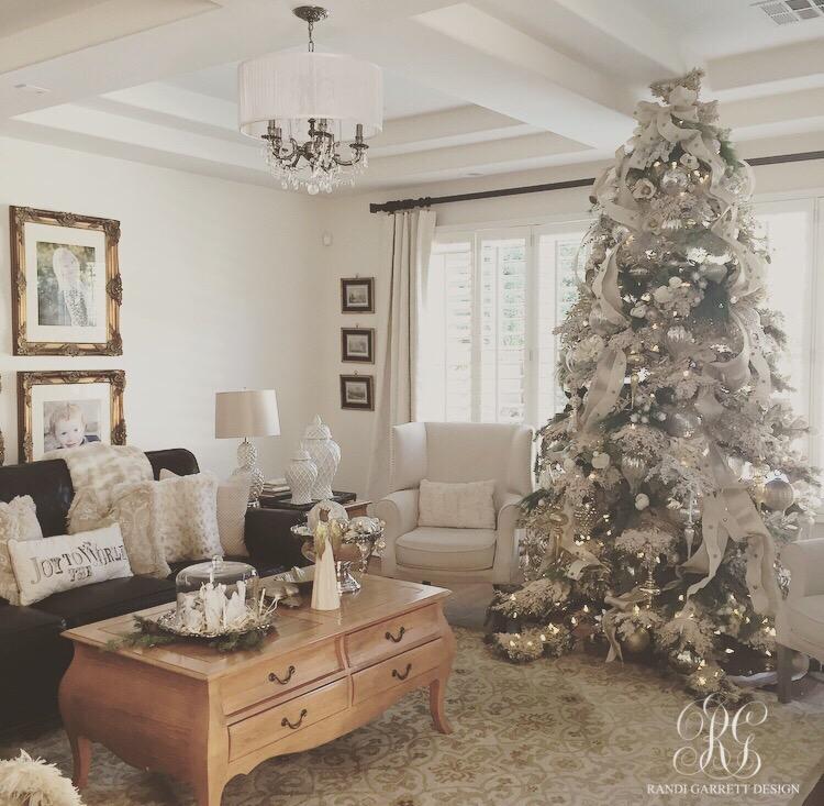 Elegant white Christmas family room with flocked Christmas tree by Randi Garrett Design