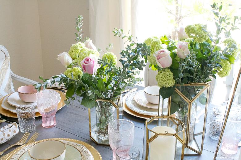 Simple floral arrangement using gold lanterns by Randi Garrett Design