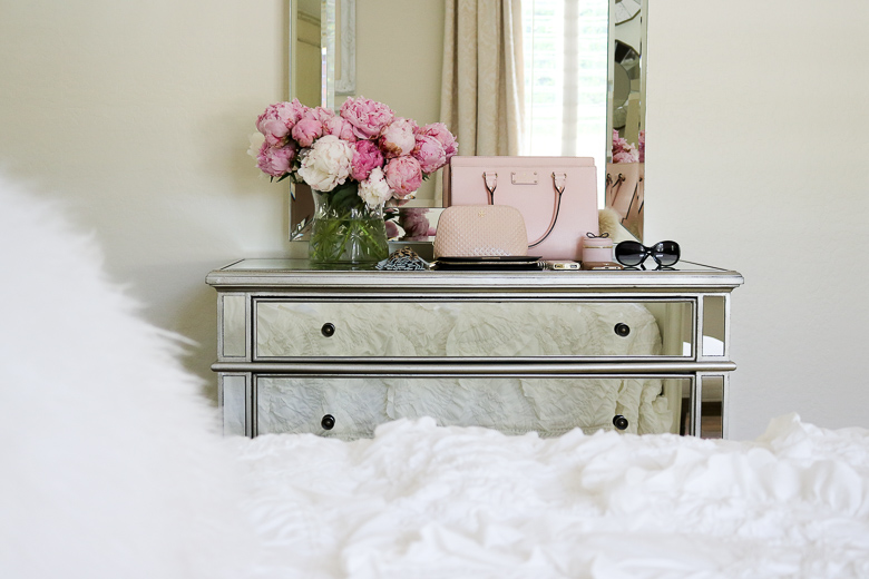 Romantic bedroom with mirrored dresser and pink purse
