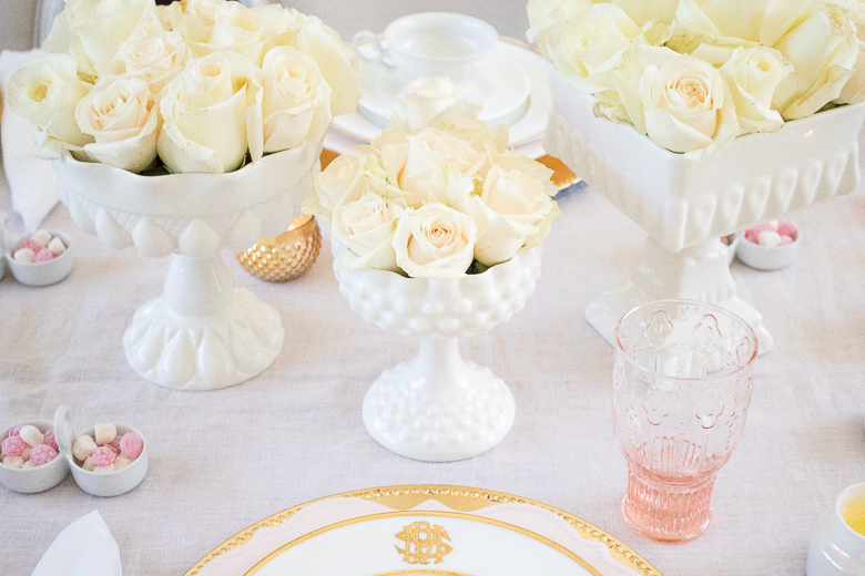 White rose centerpiece on pink and gold table
