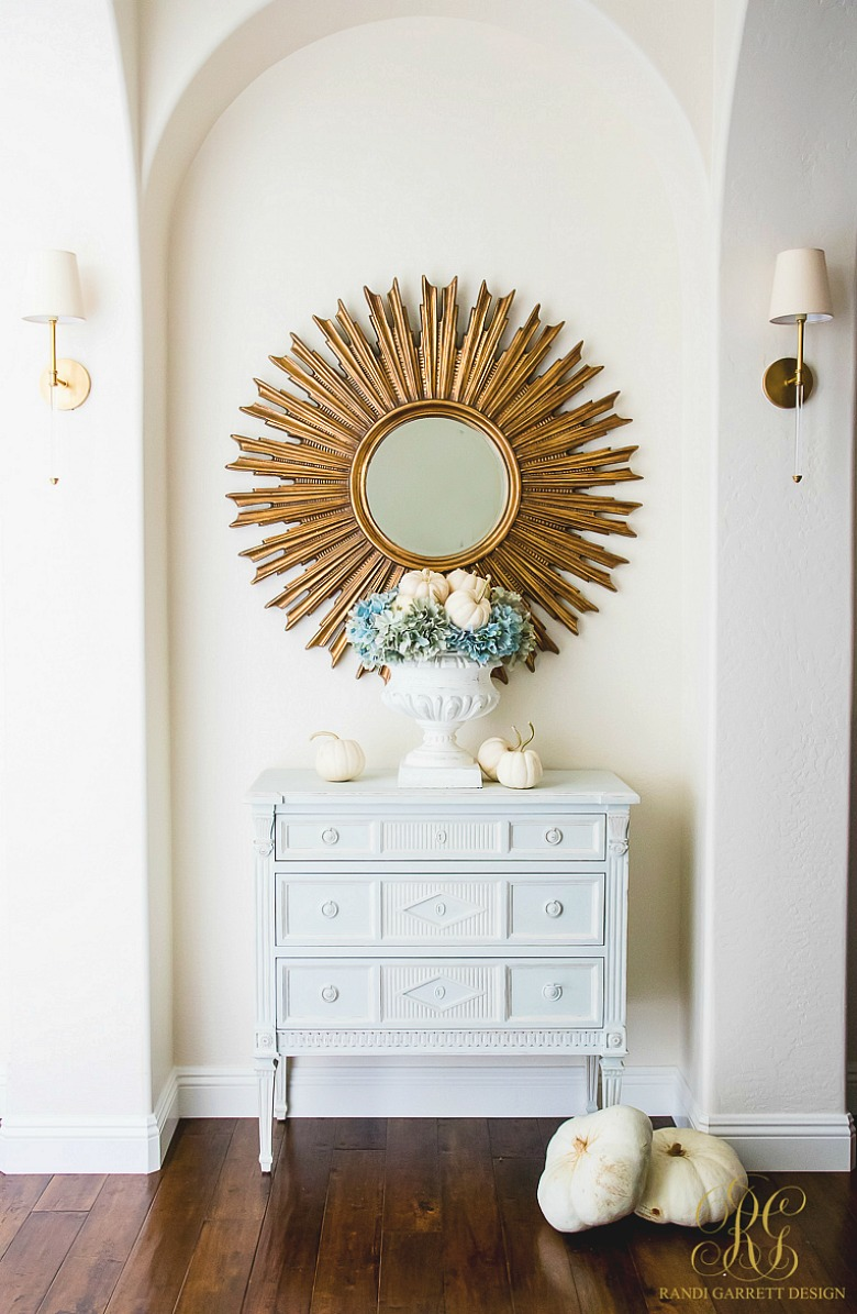 entryway styled for fall - white urn filled with baby pumpkins and hydrangeas