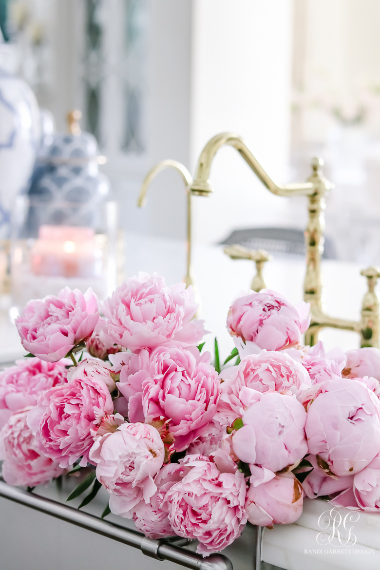 pink peonies in stainless steel sink brass faucet