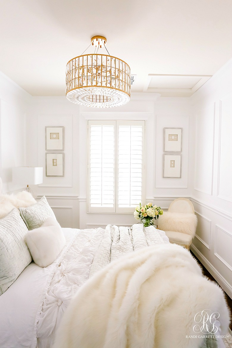 glam guest bedroom - white walls - wainscoting - glam gold crystal chandelier