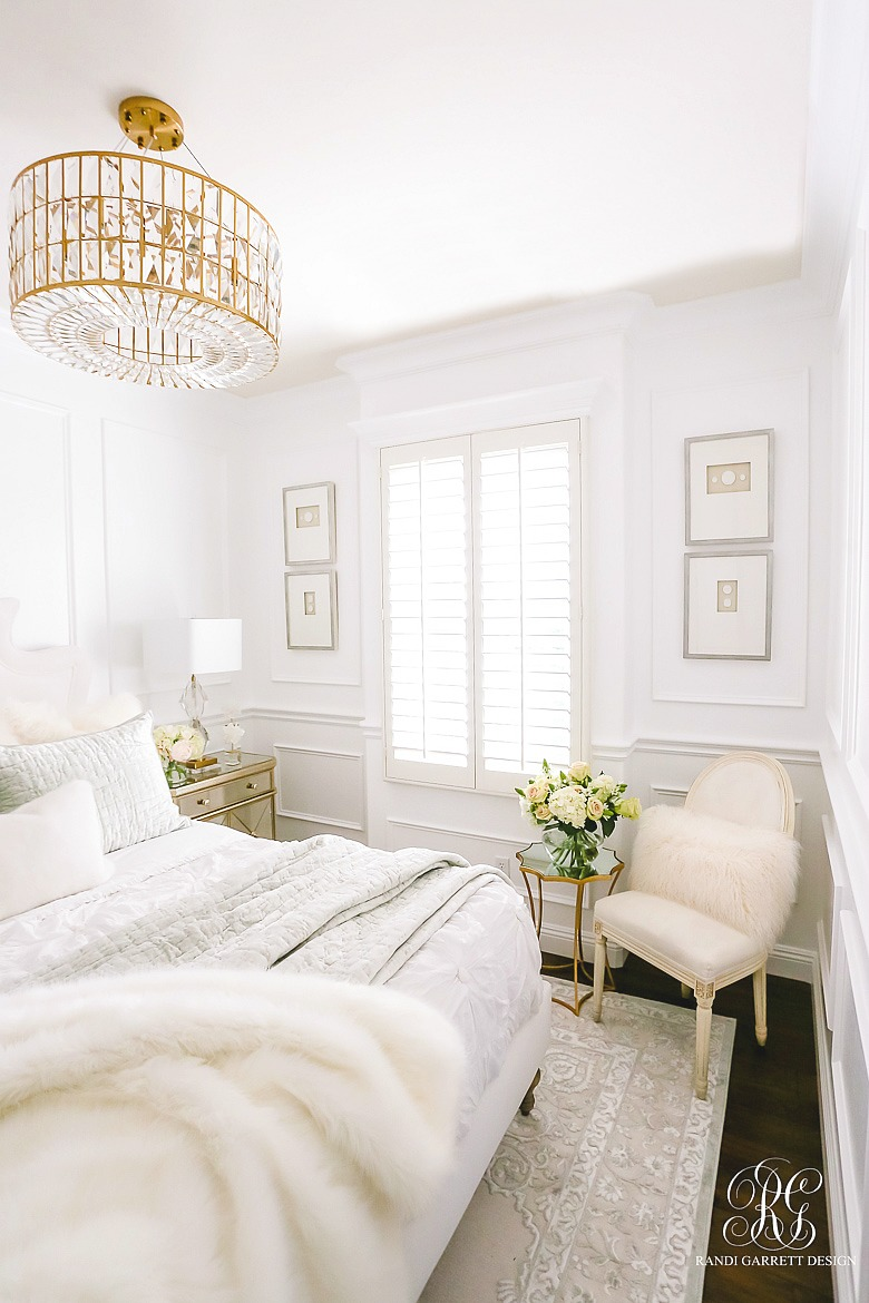 glam bedroom with white walls and wainscoting and lux bedding
