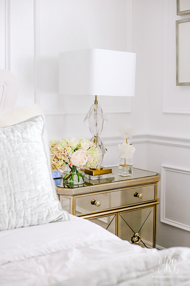 Glam guest bedroom with mirrored nightstand and velvet bed
