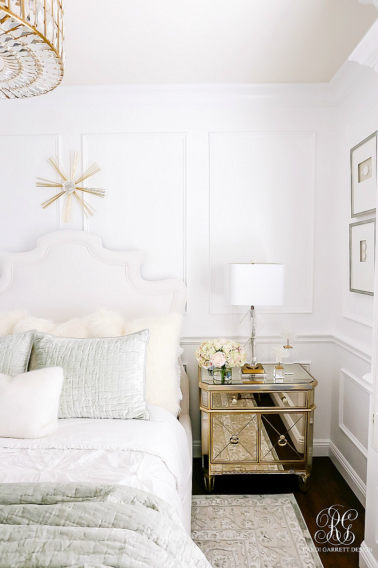 Luxe bedroom with mirrored nightstands and gold accessories and wainscoting