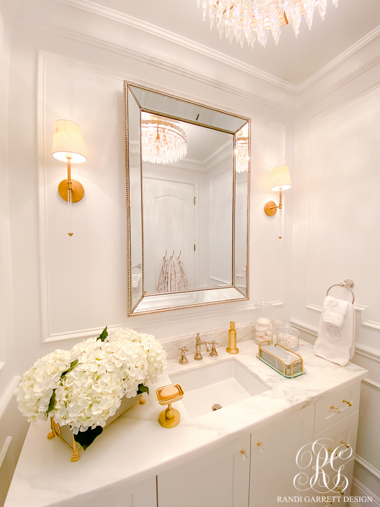 white bathroom with wainscoting gold accents